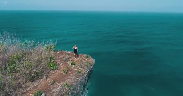 Aerial drone shot of pretty girl walking on the cliff with amazing ocean and cloudy sky view - video in slow motion