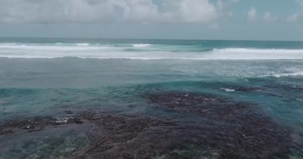 Aerial drone view of beautiful ocean waves with white water foam against cloudy sky - video in slow motion