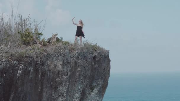 Pretty girl doing selfie photo while standing on the cliff with amazing ocean and cloudy sky view - video in slow motion