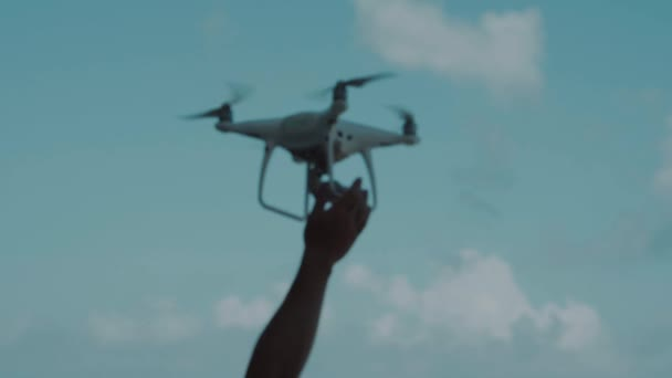 Male hand catching drone against blue summer sky background - video in slow motion