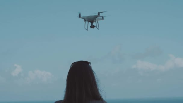 Back view of woman operating drone with remote controller and recording beautiful ocean water during sunny summer day - video in slow motion