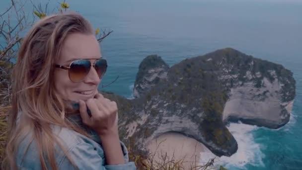 Pretty girl traveler smiling while standing over amazing Kelingking Beach cliffs in Nusa Penida, Bali, Indonesia
