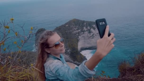 Pretty girl traveler doing selfie photo while standing over amazing Kelingking Beach cliffs in Nusa Penida, Bali, Indonesia