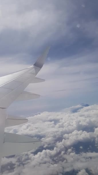 First person view of passenger looking on airplanes wing flying above the clouds - vertical view video