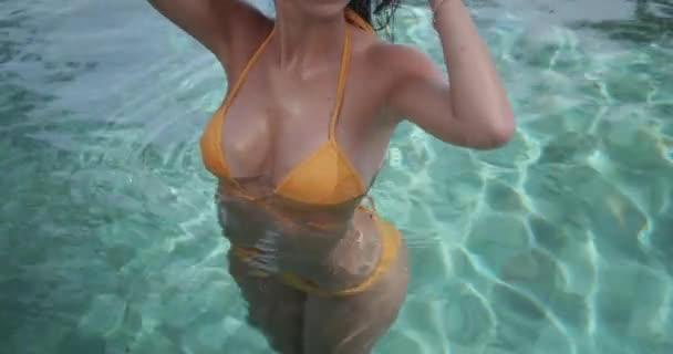 Bella giovane donna prendere il sole a bordo piscina sulla vacanza di lusso