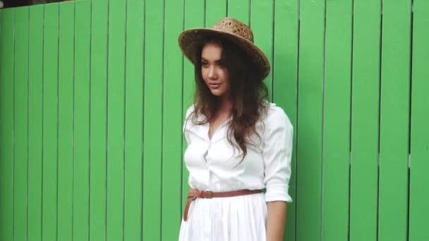 Módní krása portrét usmívající se dívka v bílých šatech a slaměný klobouk izolované světle zelená zeď