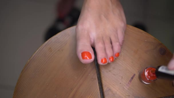 Detailní záběr ženské nohy dělat pedikúru. Dívka vyrovnávací Červený lak na nehty