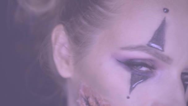 Vértes arca nő a hátborzongató Halloween bohóc smink néz a kamerába. Kreatív, művészi, Halloween koncepció - video-ban lassú mozgás