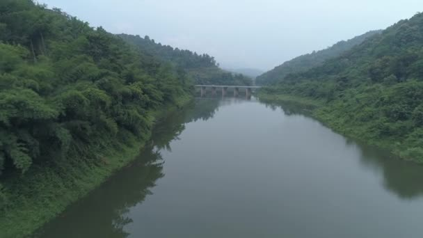 Aerial drone view of Chiang Rai area with beautiful mountains and river with dam during foggy morning, Thailand