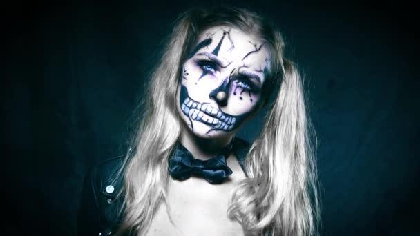 Fronte del primo piano della donna con trucco raccapricciante di Halloween  clown cranio esaminando la fotocamera  Creativo, artistico, concetto di  Halloween - video al rallentatore