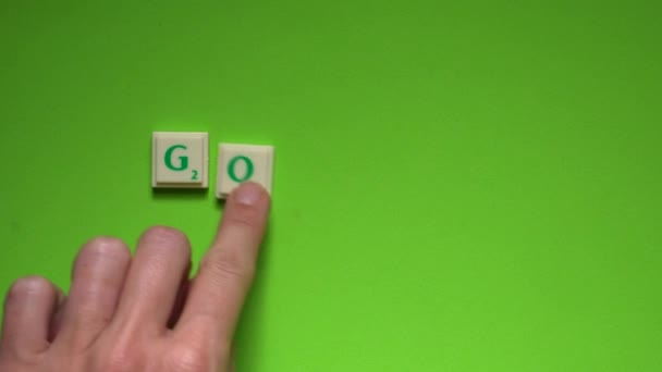 Womans hand creating word of goodbye with the letters on the green screen background