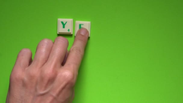 Womans hand creating words of yes or no with the letters on the green screen background