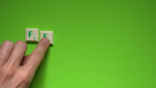 Ženská ruka vytváření slovo Únor s písmeny na zeleném pozadí