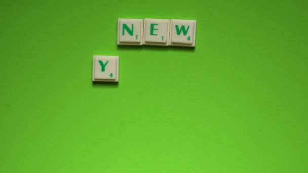 Womans hand creating words of new years resolution with the letters on the green screen background