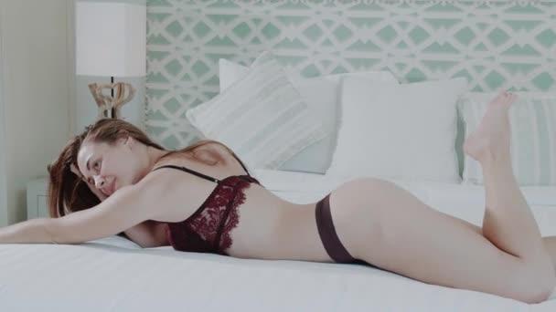 Krásné červené vlasy dívka v prádle pózuje na posteli v moderně villa dům ložnice - video v pomalém pohybu