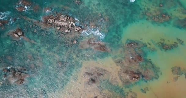 Légi drone felülnézete átlátszó sekély tengeri vízfelület és a sziklák
