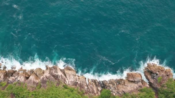 Vzdušný pohled na oceánské nádherné vlny a skalnaté pobřeží se zelenáčem
