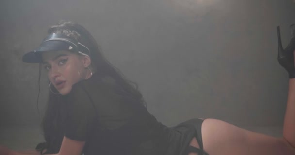 Smyslná žena v černém vidět skrz tričko, spodní prádlo a sluneční štít tančí na podlaze ve studiu s šedými betonovými stěnami-video v pomalém pohybu