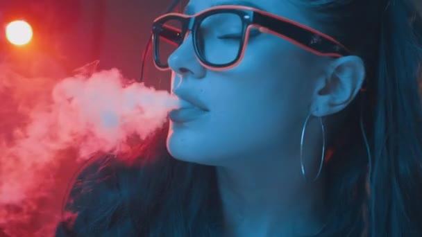Gyönyörű barna nő a dohányzás elektronikus cigaretta neon színes fény-videó lassítva