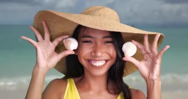Studio hell Sommer Porträt der schönen lächelnden Frau in gelbem Badeanzug und goldenem Hut spielt Gucktabu mit Muscheln über verschwommenem Meereshintergrund