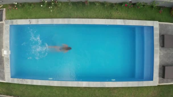Aerial drone top view of woman jumping into the swimming pool