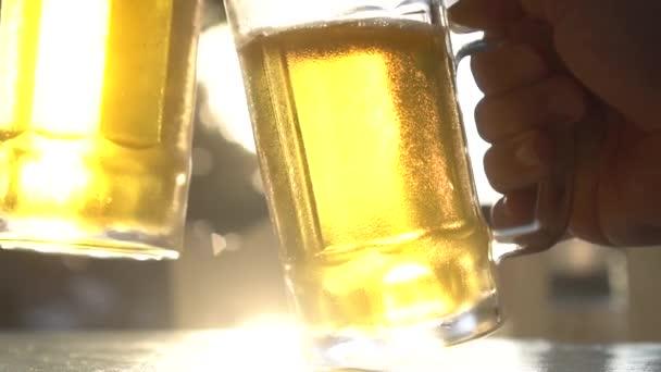 Closeup přípitek cinkání čerstvé ležáky pivní sklenice se slunečními paprsky v horkém letním dni-video v pomalém pohybu