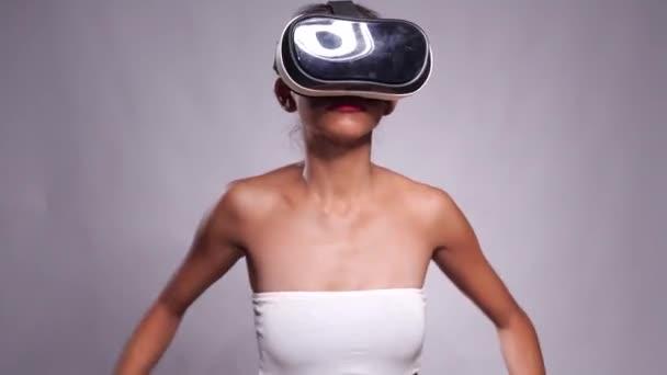Abbastanza giovane ragazza asiatica in posa con auricolare realtà virtuale o 3d occhiali isolati su sfondo grigio parete