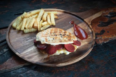 Grilled Turkish sausage and cheese panini sandwich served with fresh crispy french fries on rustic wooden kitchen table