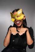 Porträt einer attraktiven jungen asiatischen Frau in goldener Katze Karnevalsmaske isoliert über Betonmauer Hintergrund