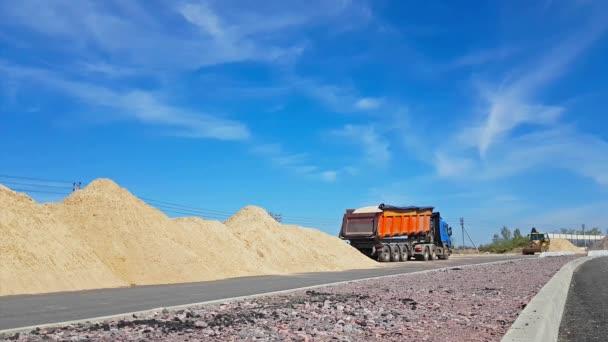Traktor lopata načte těžký náklaďák s pískem