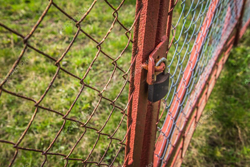 Gate closed with a padlock - focus on the padlock