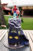 5 year baby birthday cake with spiderman on top and batman mask on table outdoor