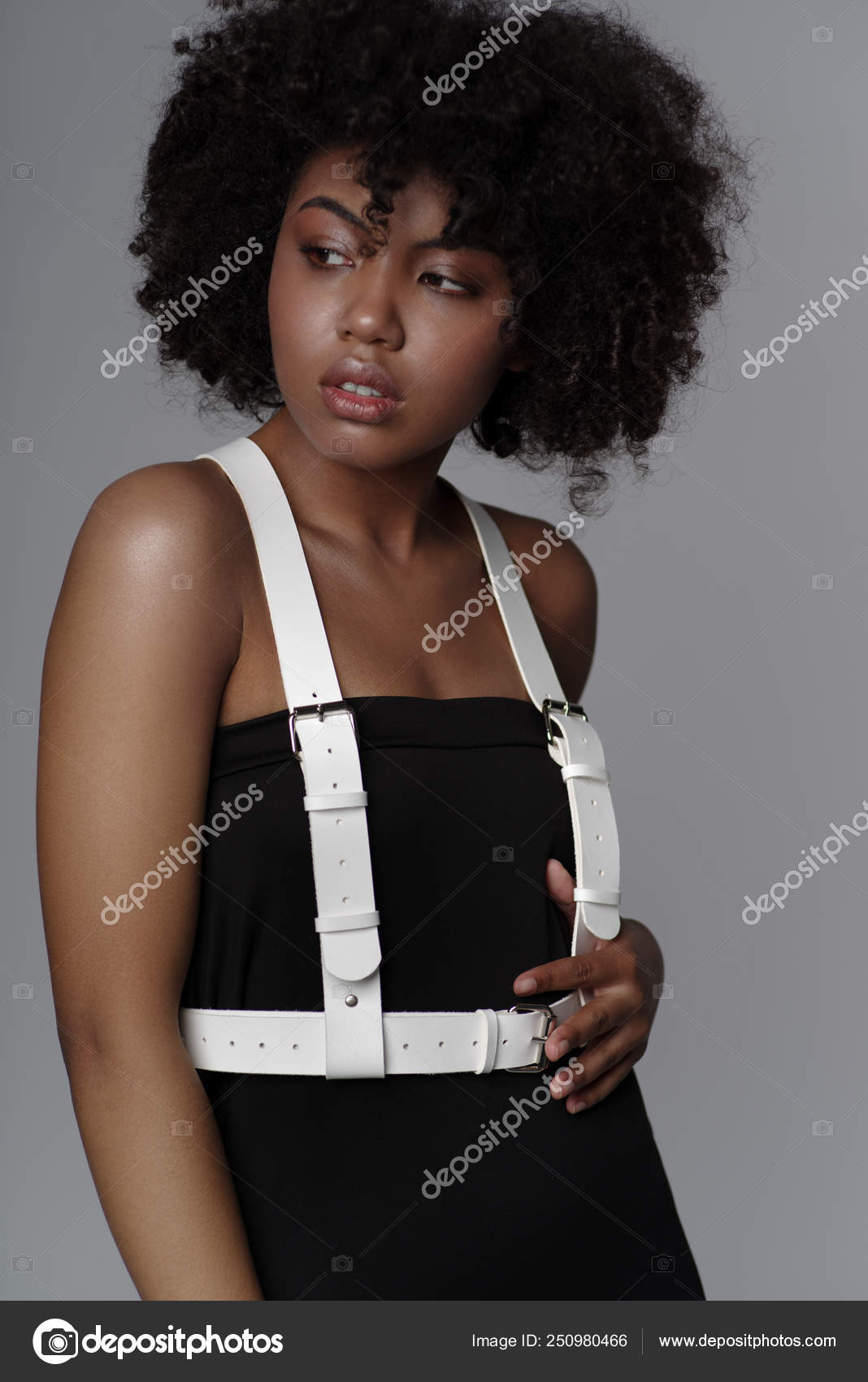b5db68f4daed9 Beautiful african american woman with curly hairstyle wearing leather female  sword belt over black dress and posing on light grey background — Photo by  ...