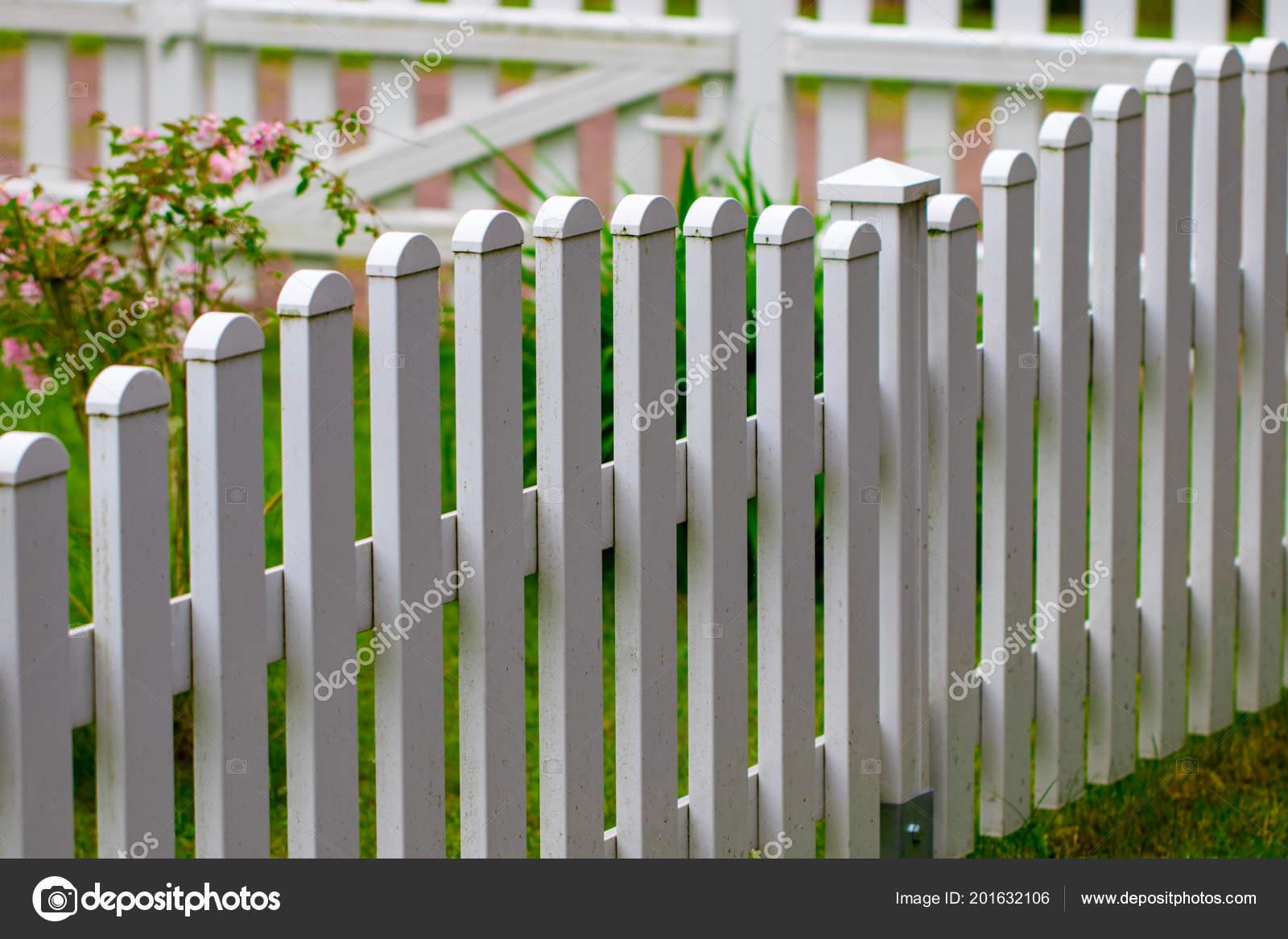 weißer zaun auf grünem gras und blumen genommen closeup — stockfoto