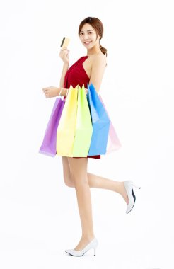 Happy young Woman with shopping bags and credit card stock vector