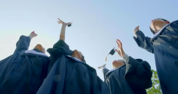 graduation students in bachelor gowns throwing mortar boards up in the air