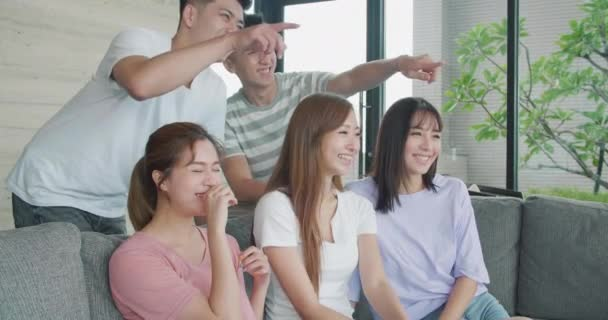 group of young people watching TV together at home