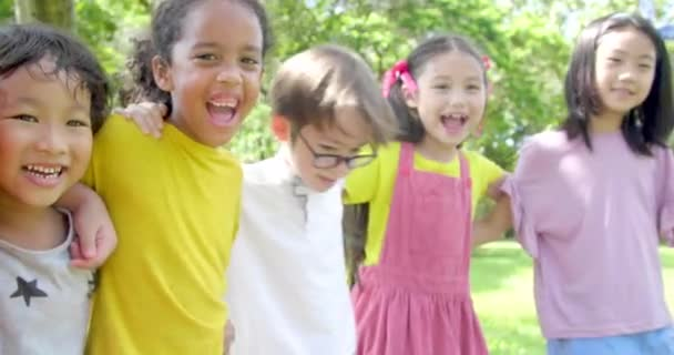 Több-etnikai csoport iskolás gyermekek nevetve és átfogó