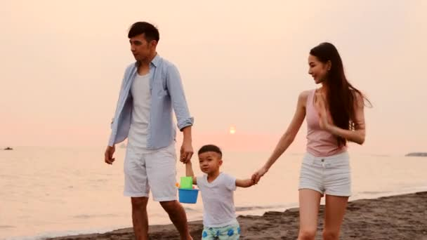 happy asian family walking on beach