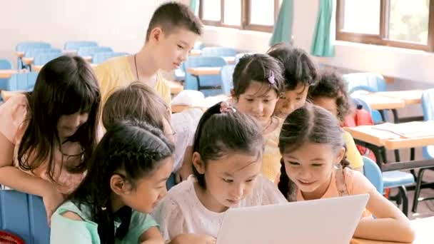 Happy children watching the laptop and discussing in the classroom