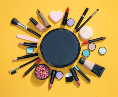 Beauty background with cosmetics for makeup. Photo of black makeup bag with cosmetic products on yellow background. Copy space for your text