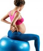 Nižší bolesti zad. Fotografie těhotné ženy držící ji zpět v bolestech izolovaných na bílém pozadí. Koncept zdravého života