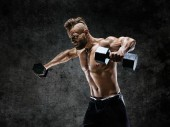 Photo Bodybuilder doing the exercises with dumbbells. Photo of young man with naked torso on dark background. Strength and motivation.