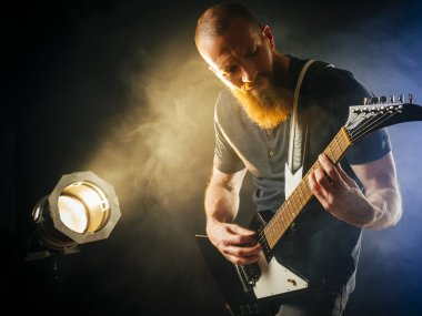 Photo of a guitar player with a beard playing in a dark club with spotlight in background.