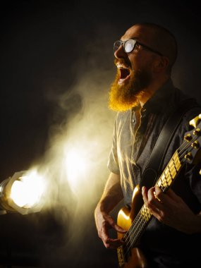 Photo of a screaming bass player with a beard playing in a dark club with spotlight in background.