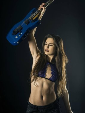 Photo of a beautiful woman holding a blue electric guitar over her head