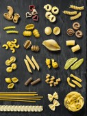 Photo of a slate board full of different types of pasta noodles.