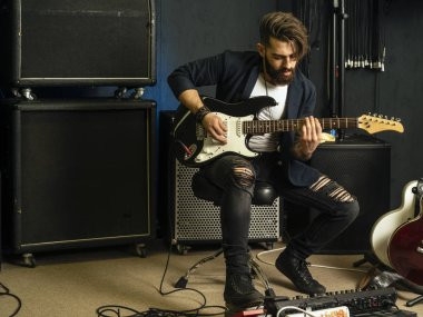 Photo of a man with beard sitting and playing his electric guitar in a recording studio.