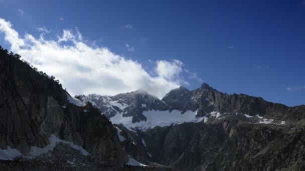 Na jaře se na summitech na vrcholných horách Rozostřívá oblaka. Pohled na vrchol Trois Vysillerů, vrchol Nouvielle a vrchol Ramougns. Modrá slunná obloha s bílými mraky.