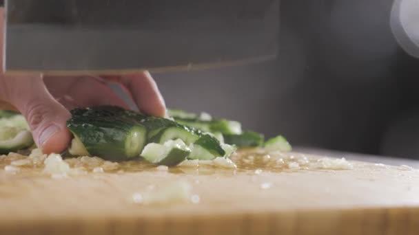 Kéz eltalálja az uborkát egy nagy késsel.